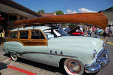 Rare 1951 Buick Super Estate Wagon woodie exhibited in a classic car show on a sunny summer day under blue skies
