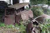 Rough pickup truck cab and fenders stored in vintage car salvage yard