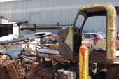 1950's truck cab and acres of original parts for vintage cars and trucks in old car salvage yard