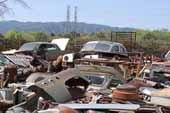 Antique project cars piled and stored in classic car junk yard