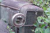 Radiator shell and original headlamp on Ford pickup truck in classic car salvage yard