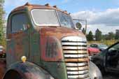 Heavy-duty GMC COE truck in vintage car wrecking yard