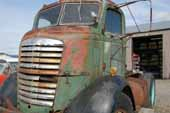 Rare GMC COE truck parked in classic car and truck salvage yard