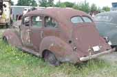 Straight 1940's 4-door sedan in vintage car wrecking yard and ready for restoration