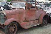 Restorable original 1929 Ford Model A roadster parked at vintage car junkyard