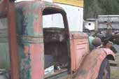 1936 Chevy tow truck parked at vintage car wrecking yard