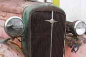 Nice original vintage radiator and trim on 1936 Chevy truck in vintage car junk yard