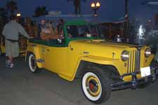 Cool vintage Willys Jeepster towing a small trailer full of carved tikis for sale at the beach in Huntington