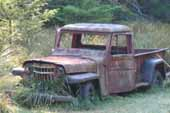 Original 1950's Willys Overland Jeep pickup truck in old car wreckingyard